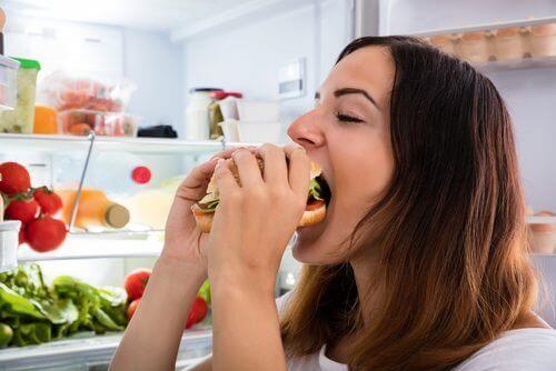 sandviç yiyen kadın buzdolabı