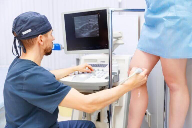 doktor kadının bacağı üzerinde çalışıyor