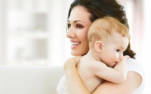 yeni doğan bebeğini tutan anne