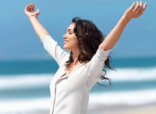 kollarını açmış mutlu kadın deniz kenarı