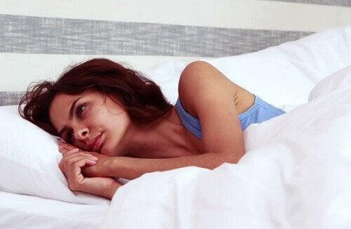 yatakta yan dönmüş yatan mutsuz kadın