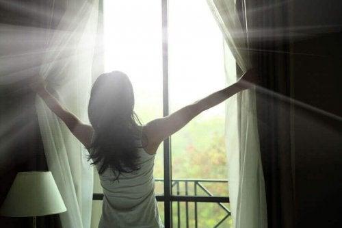 perdeleri açan kadın gün ışığı