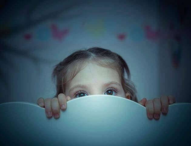 çocuk yataktan bakıyor korkmuş