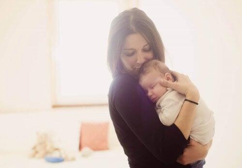 bebeği kafasından öpen anne