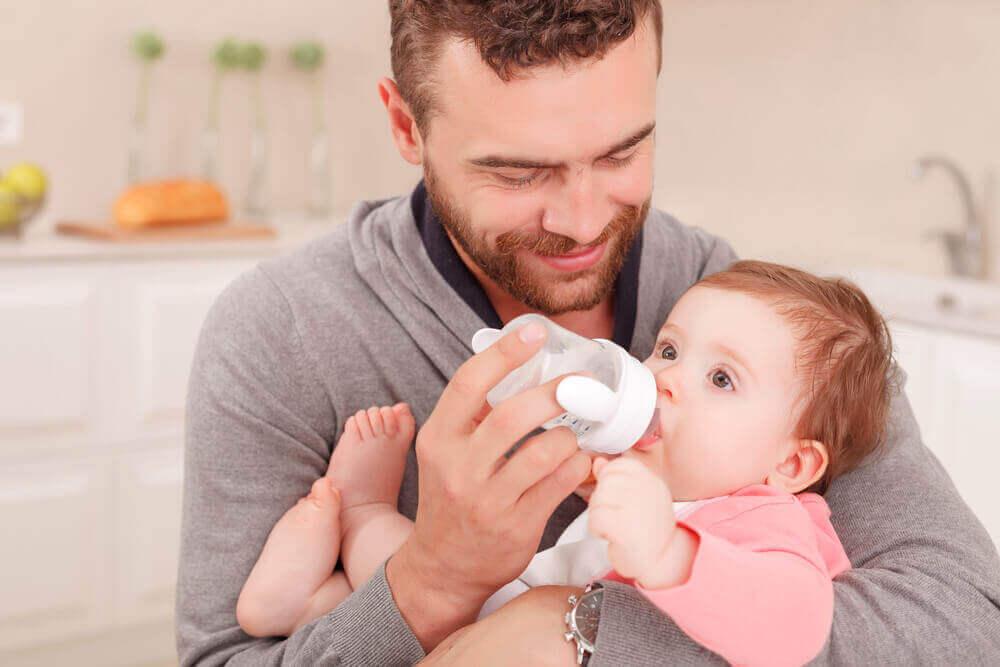 bebeğe biberon veren adam