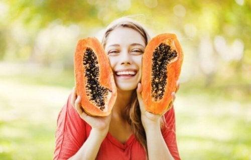 elinde ikiye bölünmüş papaya tutan kadın