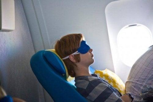 koltuğunu yatırmış bir genç ve uçakta uyumak