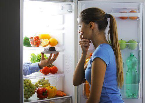 buzdolabında tatlı düşünen kadın