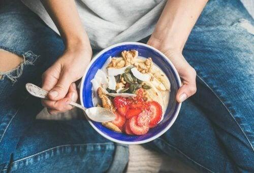 kahvaltıda meyve ve yulaf yiyen kadın