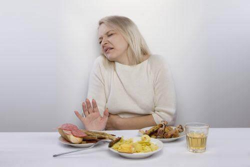 midesini tutan kadın iştahsız yemekler