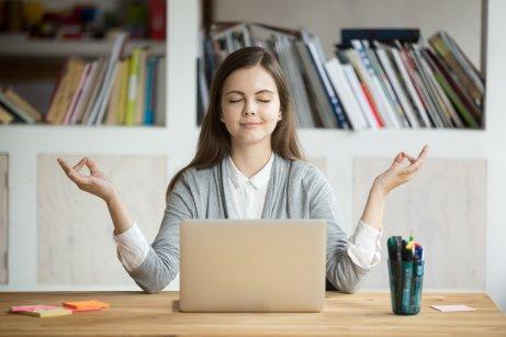 bilgisayar başında meditasyon yaparak stresi yöneten kadın