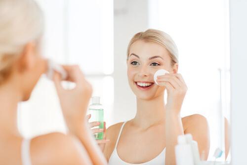 temiz ve pürüzsüz cilt için yüzüne toner uygulayan kadın