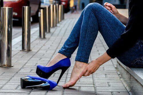 sokakta ayağından ayakkabısını çıkaran kadın