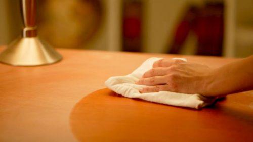 ahşap masayı temizleyen kişinin eli