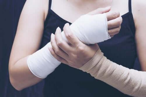 bandajlı kolu ile alçılı elini tutan kadın