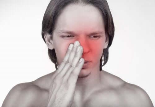 burnunu tutan adam