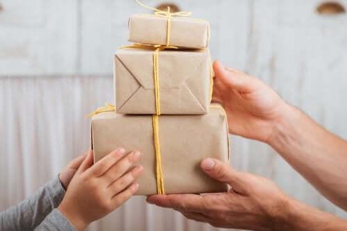 Farklı boyutlarda üç hediye kutusunu tutan iki çift el.