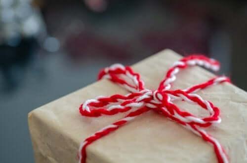 Kırmızı beyaz kurdeleli bir hediye kutusu.