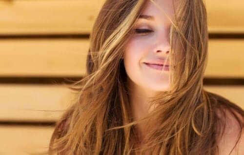 saçları uçuşan gülümseyen kadın sağlıklı bir saç derisi