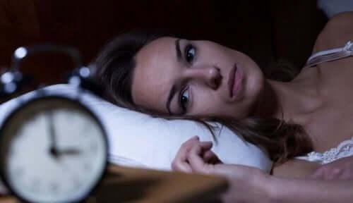 çalar saate bakan uykusuz kadın