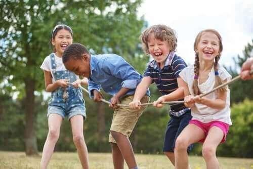 Halat çekme oyunu oynayan dört çocuk.