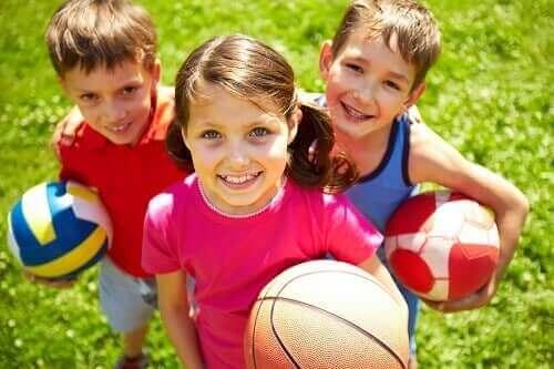 Toplarla oynayan üç çocuk.