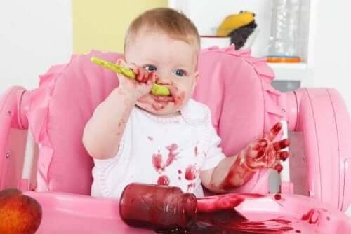 Yediği şeyi üstüne başına bulaştırmış bir bebek.