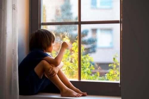 Pencerenin yanına oturmuş dışarıya bakmakta olan bir çocuk.