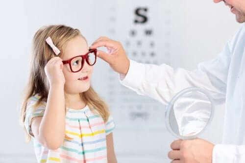 Göz doktoru ile birlikte gözlük deneyen bir kız çocuğu.
