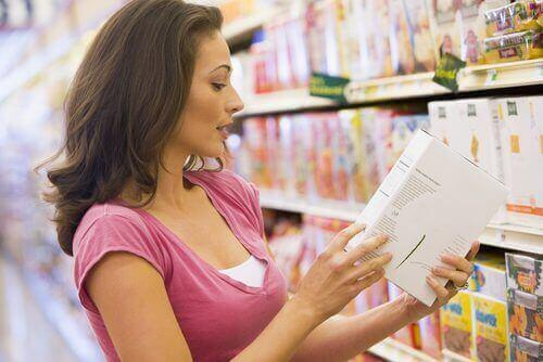 Bir yiyecek paketinin içindekiler kısmını okuyan bir kadın.