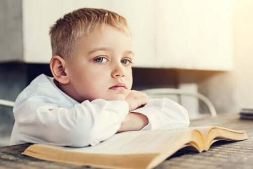 Kitabının üzerine yatmış, sıkkın görünen bir oğlan çocuğu.
