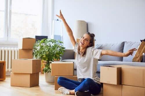 Taşınma sırasında kutuların ortasında oturan bir kadın.
