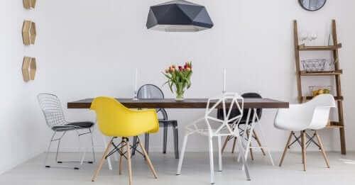 Etrafında farklı renkler ve desenlerde sandalyeler olan bir masa.