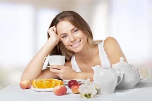 Meyve yiyen ve çay içen kadın