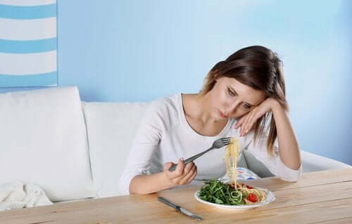 yemekle oynayan üzgün kadın
