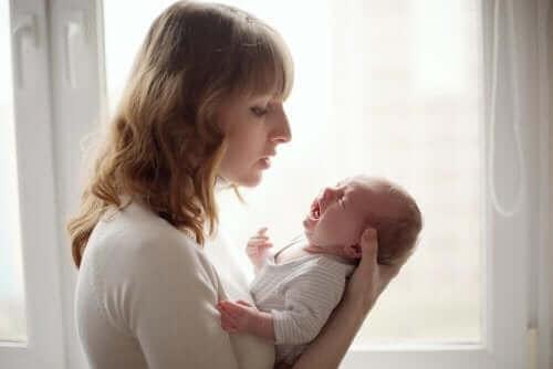 ağlayan bebeğini sakinleştiren anne