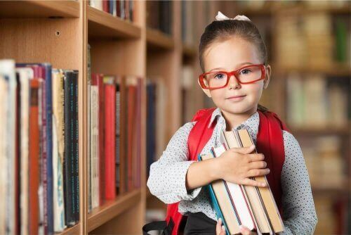 elinde kitaplar olan kırmızı gözlüklü küçük kız