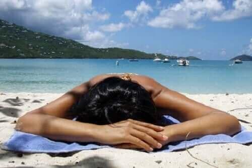Sahilde güneşlenen bir kadın.