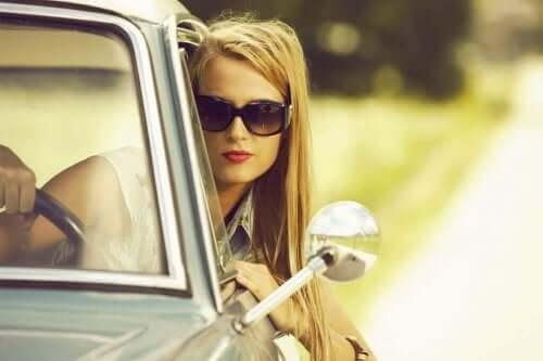 Kafasını camdan dışarı çıkarmış bir şekilde araba süren bir kadın.