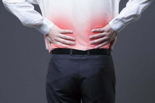 arkası dönük sırtını tutan adam ağrıyı iyileştirmek