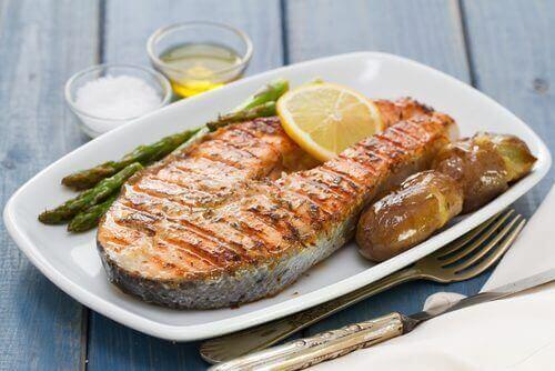 Bir tabakta sunulmuş balık, patates ve kuşkonmaz.