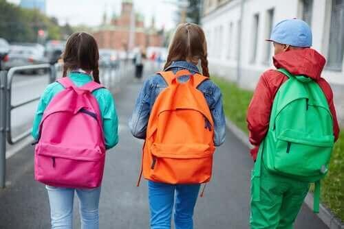 pembe, turuncu ve yeşil sırt çantaları takan üç çocuk