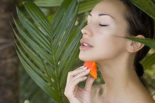 Cildine papaya süren bir kadın.