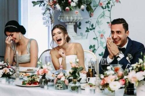 Bir masada yan yana oturan gelin, damat ve düğün misafirlerinden biri.
