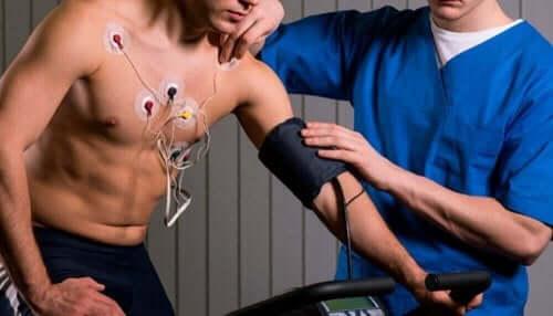 Egzersiz yapan bir adamı gözetim altında tutan bir tıbbi personel.