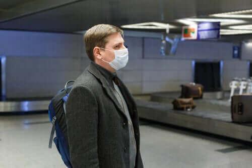 havaalanında bavul beklerken maske takmış olan adam