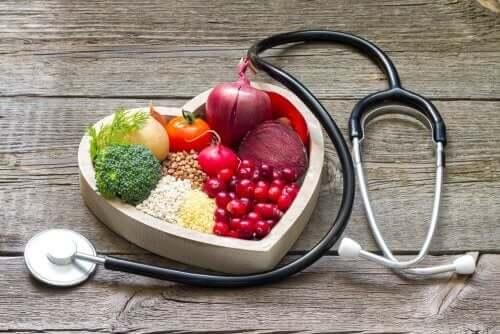 kalp şeklindeki kasede sağlıklı meyve ve sebzeler ve etraflarında bir stetoskop