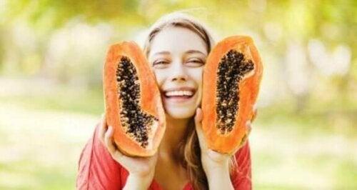 Ellerinde ikiye bölünmüş bir papaya tutan bir kadın.