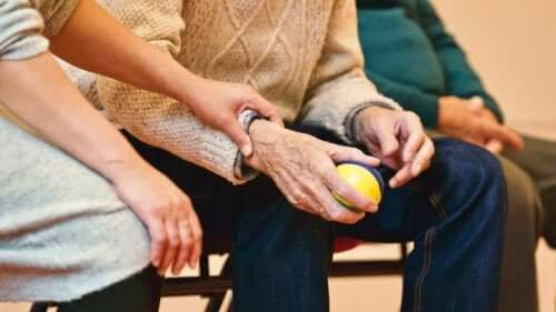 Parkinson hastalığı olan bir adamın elini tutan bir kadın.