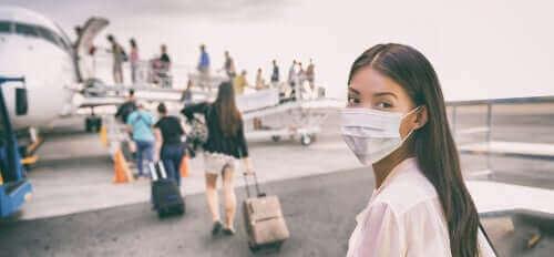 uçağa binerken maske takmış kadın